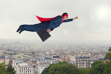 superhero businessman flying above a city