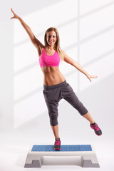 Beautiful fitness model working out on aerobic step