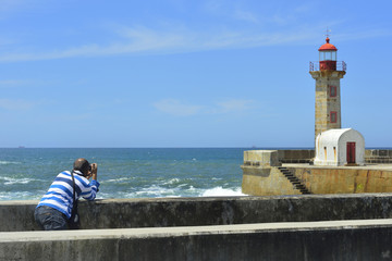 tourist photographing an ancient coastal lighthouse in Portugal