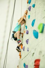 Fototapeta girl climbing up the wall obraz