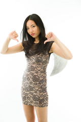 Asian young woman dressed up as an angel showing thumbs down