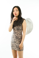 Asian young woman dressed up as an angel with finger on lips