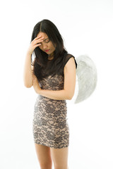 Upset Asian young woman dressed up as an angel with her head in