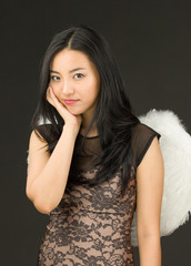 Asian young woman dressed up as an angel with her hands on cheek