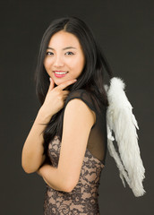 Asian young woman dressed up as an angel with her hand on chin