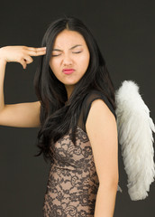 Asian young woman dressed up as an angel shooting herself in