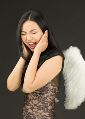 Asian young woman dressed up as an angel shouting in frustration