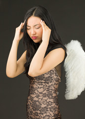 Asian young woman dressed up as an angel suffering from headache
