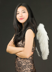 Side profile of a Asian young woman dressed up as an angel with