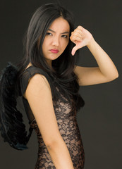 Upset Asian young woman dressed up as a black angel showing