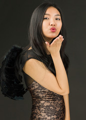 Side profile of a Asian young woman dressed up as a black angel