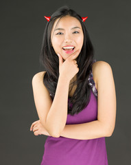 Devil side of a young Asian woman standing with hand on chin and