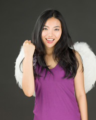 Angel side of a young Asian woman celebrating success with fist