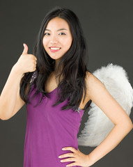 Angel side of a young Asian woman showing thumbs up sign and
