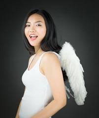 Side view of a Asian young woman dressed up as an angel smiling