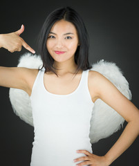 Asian young woman dressed up as an angel pointing herself with