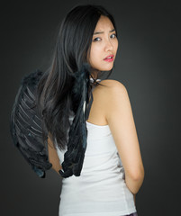 Rear view of a Upset Asian young woman dressed up as an angel