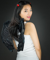 Rear view of a Asian young woman dressed up as an devil turning