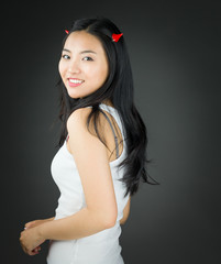 Side view of a Asian young woman in devil horns and smiling