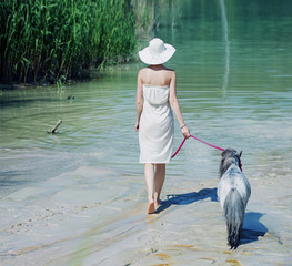 Shapely woman walking with the pony