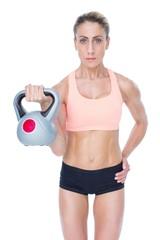 Serious female crossfitter lifting kettlebell