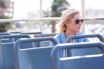 thoughtful young woman on open top bus