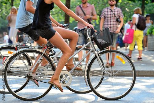 Fototapete Summer couple on bikes in green city