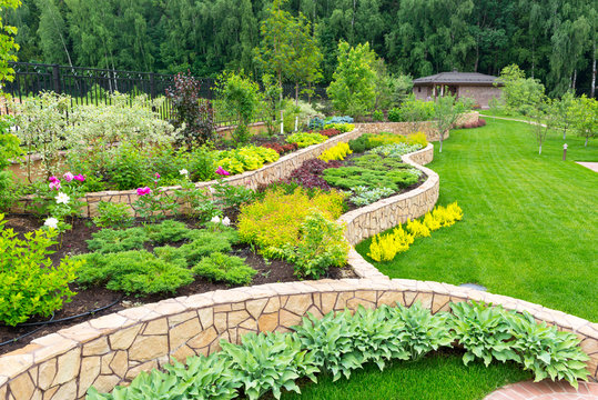 Landscape design in home garden, beautiful landscaping in backyard in summer
