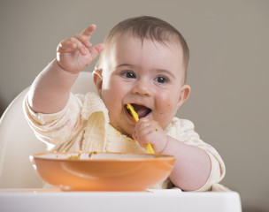 a cute baby girl laughing during meal time