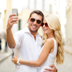 smiling couple taking selfie with smartphone
