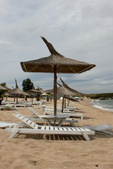 Empty beach with wicker umbrellas and sunbeds