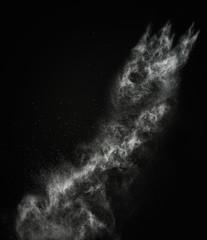 White powder exploding isolated on black