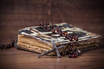 Christian cross necklace next to prayer-book
