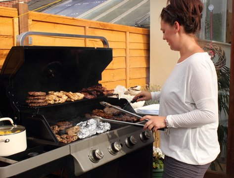A young woman cooking on the bbq