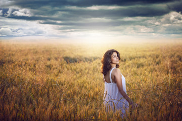 Beautiful woman in corn field with dramatic light