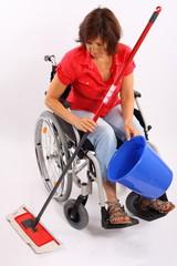 Frau im Rollstuhl putzt