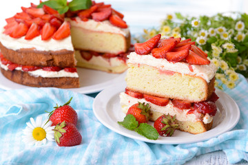 Delicious biscuit cake with strawberries on table close-up