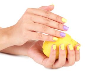 Female hands with stylish colorful nails holding fresh lemon,