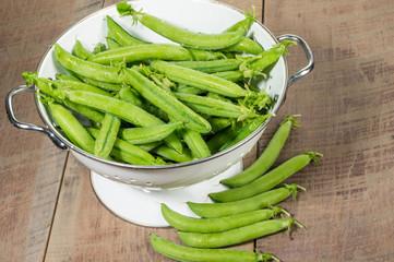Fresh peas in a white colander
