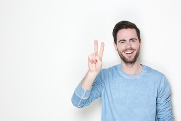 Young man smiling with victory sign