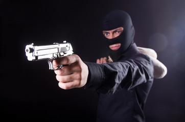 Man wearing balaclava with gun