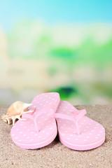 Color flip-flops on sand, on nature background