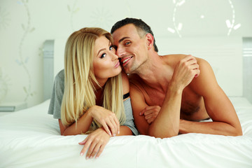 Loving young couple lying on the bed at home