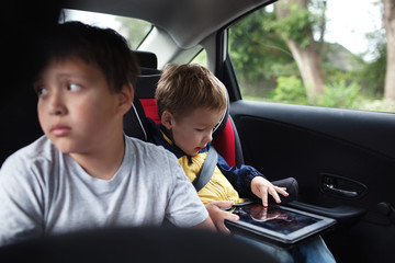 Two boys traveling on the back seat of a car
