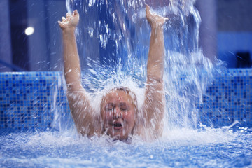 Woman under water stream in the swimming pool
