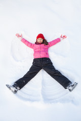 young girl laying on snow and making angel.