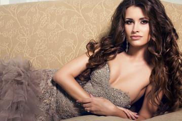 sexy beautiful woman in luxurious dress lying on divan