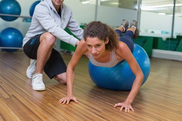 Trainer helping his client doing push up on exercise ball