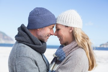 Attractive couple smiling at each other on the beach in warm clo