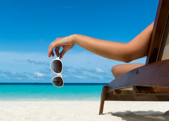 Young girl lying on a beach lounger with glasses in hand